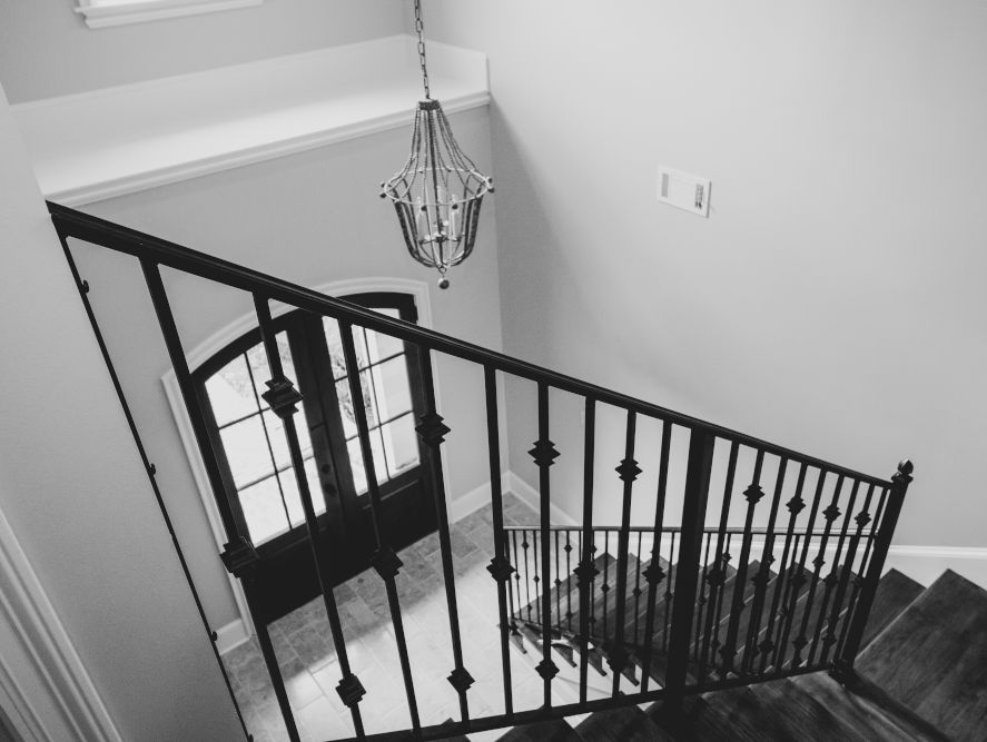 looking down from a staircase with chandelier