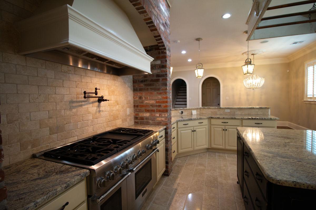 spacious kitchen with brick, ceramic, and granite